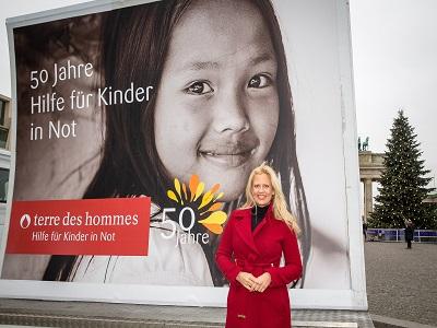 Barbara Schöneberger vor Plakat von terre des hommes
