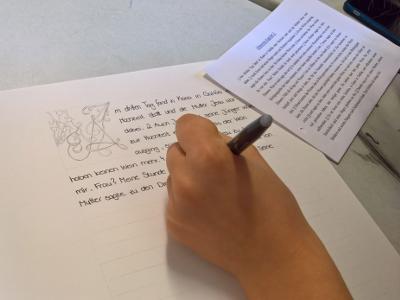 Bild: Schüler schreiben das Evangelium ab, Foto: Mario Brumbi