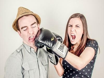 Frau schlägt Mann mit Boxhandschuh