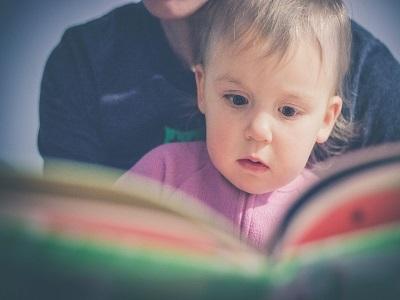 Kind schaut mit Mutter ein Bilderbuch an