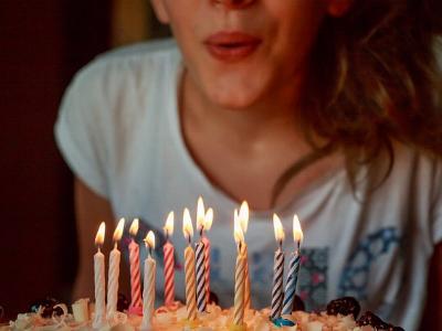 Mädchen pustet Kerzen auf dem Geburtstagskuchen aus