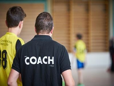 Ein Trainer mit einem Sportler in der Turnhalle