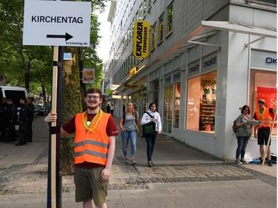 Ein Helfer des Kirchentags mit einem Wegweiser in der Dortmunder Innenstadt