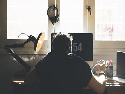 Blick von hinten auf Mann der am Schreibtisch sitzt