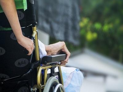 Mensch schiebt einen Rollstuhl