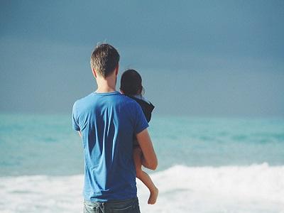 Vater mit Kind auf dem Arm steht am Strand