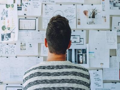 Ein Mann steht vor einer Wand voller Pläne