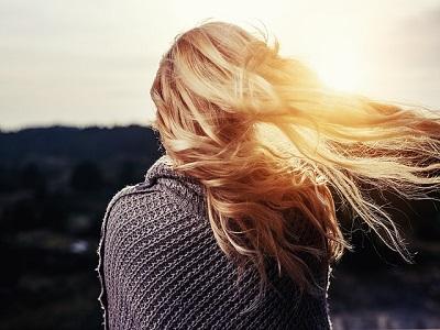 Rueckenansicht von Frau mit wehenden Haaren