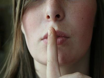Frau hält Zeigefinger an den Mund