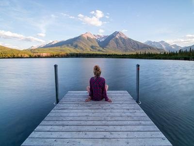 Frau sitzt auf Steg vor See