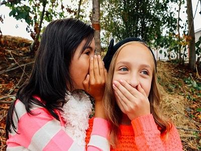 Ein Mädchen flüstert einem anderen etwas ins Ohr