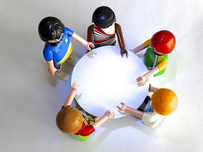 Playmobilfiguren um einen Tisch drapiert